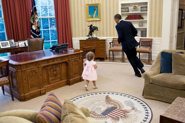 Vị Tổng thống đang chạy quanh chiếc bàn trong trò chơi đuổi bắt với người bạn váy hồng đáng yêu.