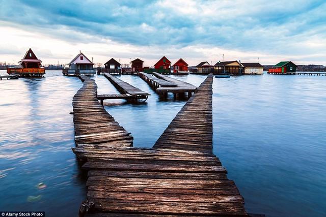 """Nằm ở tây nam thủ đô Budapetst của Hungary là một 'bộ sưu tập"""" những ngôi nhà cabin nằm trên những cây cột và được biết tới với cái tên """"ngôi làng nổi""""."""