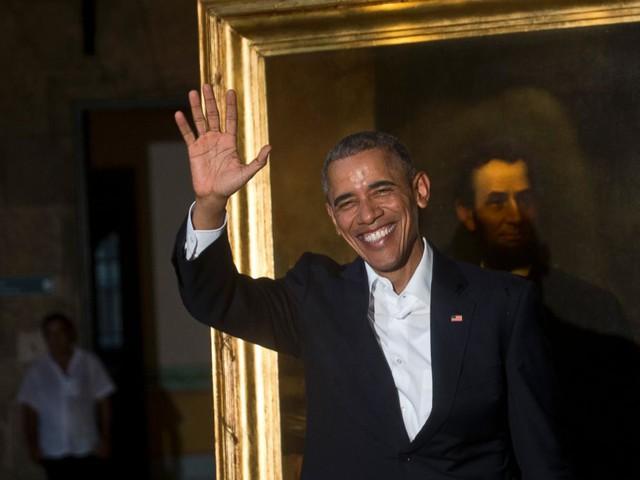 Tổng thống Obama vẫy chào các phóng viên khi đang đứng cạnh bức tranh vẽ Tổng thống Abraham Lincoln trong chuyến thăm Bảo tàng thành phố Havana (Ảnh: AP)