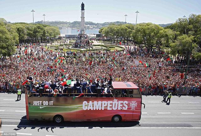 Hàng vạn CĐV đừng dọc hai bên đường nơi chiếc xe chở các nhà vô địch EURO đi qua.