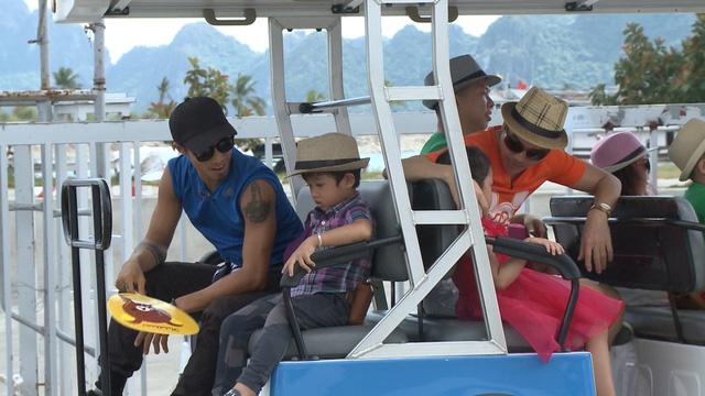 Các gia đình di chuyển bằng xe điện về chỗ nghỉ.