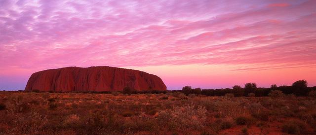 Từ sáng sớm đến lúc chạng vạng tối, màu sắc của ánh sáng thay đổi trên vách núi Uluru. Ảnh: lifehack.