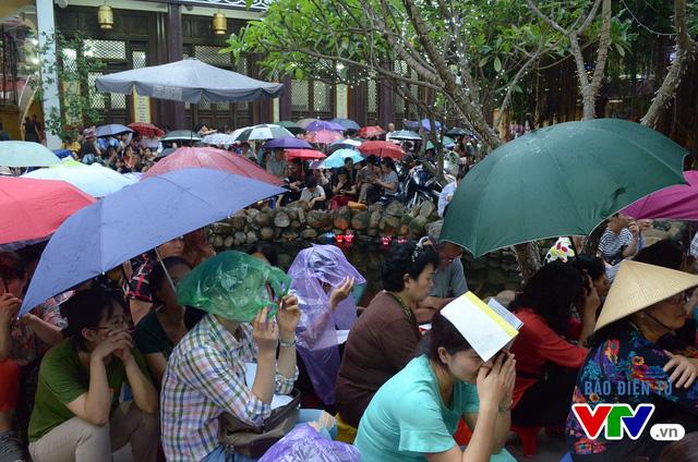 Khoảng 18h, dù trời đã bắt đầu đổ mưa những người đi lễ vẫn sẵn sàng ngồi ngoài sân để chờ làm lễ