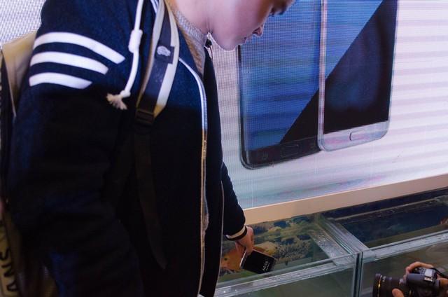 Người dùng đầu tiên đang thả chiếc điện thoại xuống bể cá ngay sau khi mua