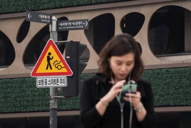 Một biển cảnh báo nguy hiểm cho người mải dùng điện thoại tại một ngã tư ở Seoul. (Ảnh: AFP)