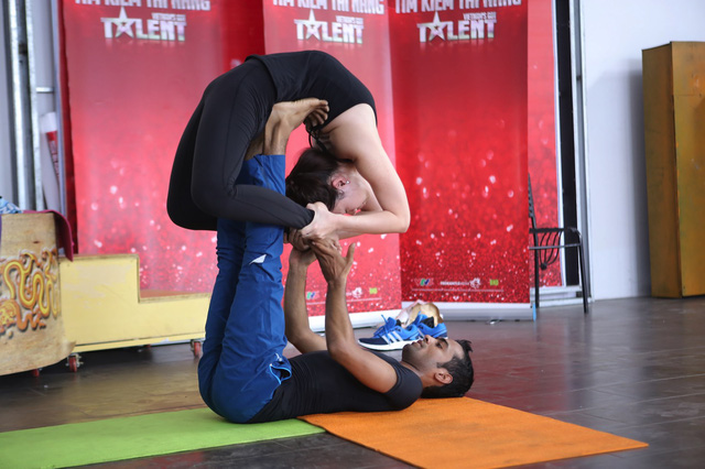 Gaurav Sharma tập luyện màn trình diễn yoga nâng đỡ một người khác.
