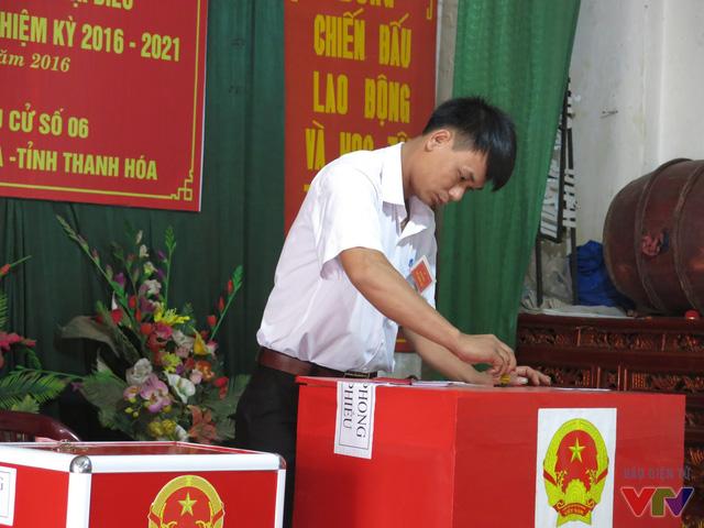 Sau khi tuyên bố khai mạc điểm bầu cử, đại diện hội đồng bầu cử dán giấy niêm phong hòm phiểu trước sự chứng kiến của người dân.
