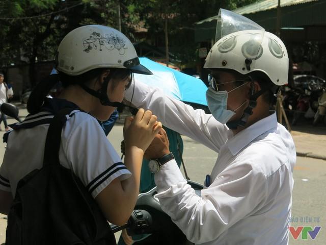 Người nhà ân cần tháo mũ bảo hiểm cho thí sinh sau khi đưa tới trường thi.