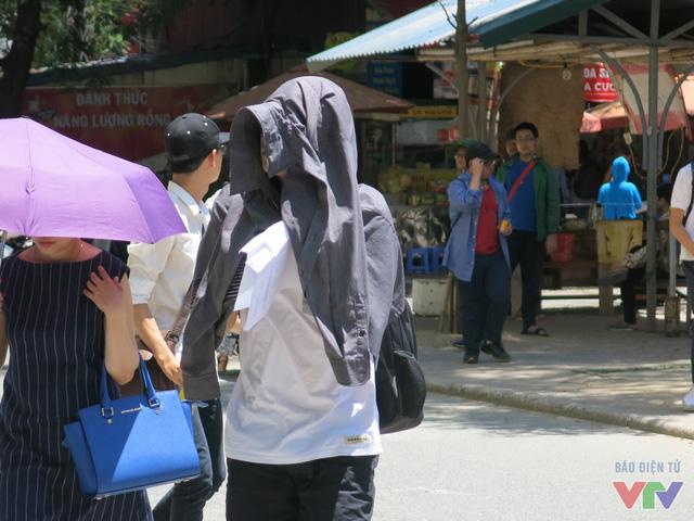 Một thí sinh phải dùng áo trùm lên đầu che nắng gắt.