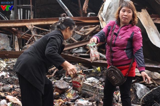 Các tiểu thương lục tìm trong đống đổ nát những gì còn sót lại sau vụ cháy