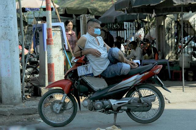 Để tránh nắng và khói bụi, người xe ôm này luôn phải đeo khẩu trang kín mặt trong lúc chờ khách.