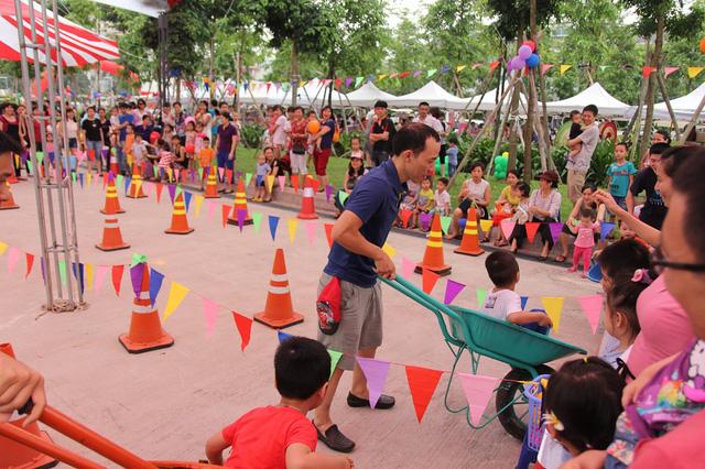 Ở khu vực khác, nhiều ông bố cùng các con tham gia trò chơi vận động Đẩy xe nhặt bóng