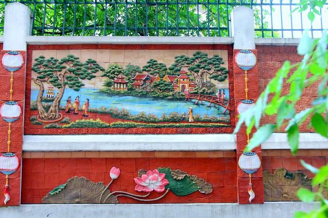 Về chiều dọc, bức tưởng chia thành 2 phần, phần trên là các bức tranh về phong cảnh làng quê, bên dưới là các bức tranh hoa sen nhỏ hơn