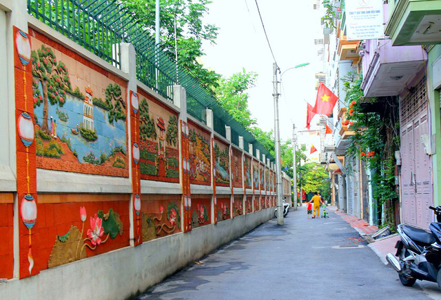 Toàn bộ phần mặt tường dài khoảng 200m chạy dọc trước cửa các hộ dân (mặt sau của trường THCS Dịch Vọng Hậu) được phủ lên bằng những bức tranh khổ lớn đẹp mắt và tinh tế
