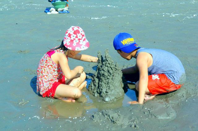 Nhiều em nhỏ thích thú nghịch cát trên bờ biển sau khi tắm