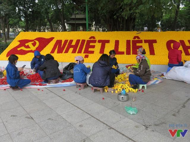 Tại vườn hoa Lê Nin, các công nhân đang gấp rút cắm hoa hoàn thiện dòng chữ Nhiệt liệt chào mừng Đại hội Đảng XII.