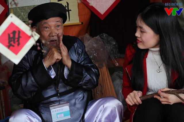Gian hàng của một ông đồ già được nhiều khách tới tham quan và xin chữ.