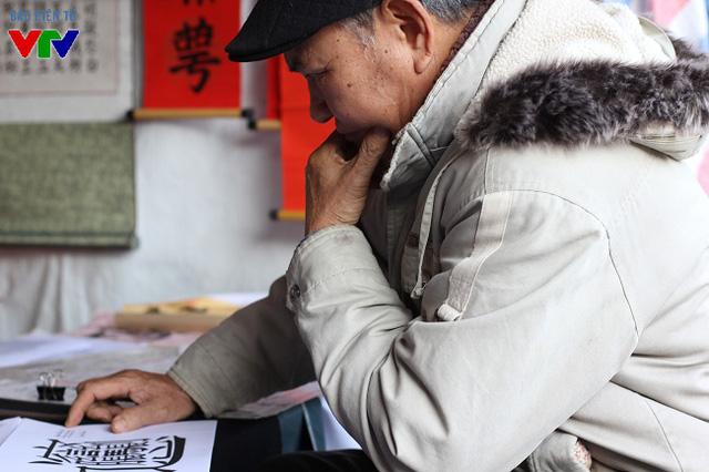 Một cụ ông đang chăm chú quan sát và phân tích tài nghệ thư pháp của các ông đồ trong Hội chữ.