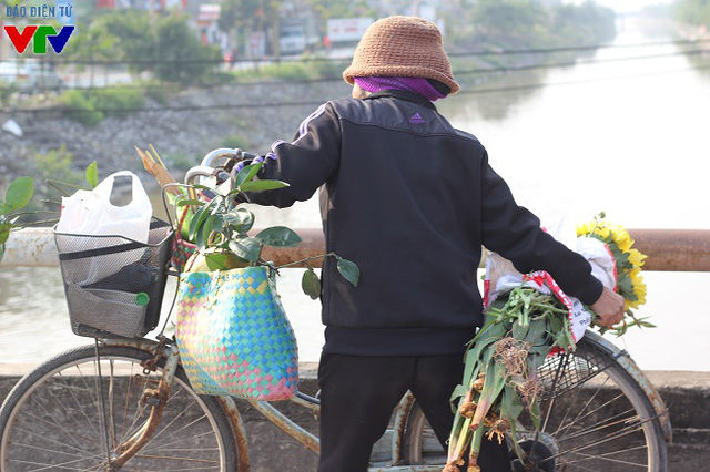 Sau phiên chợ Tết, người dân tay xách nách mang với đủ các loại hàng hóa như hoa tươi, vàng, hương, thực phẩm ăn Tết