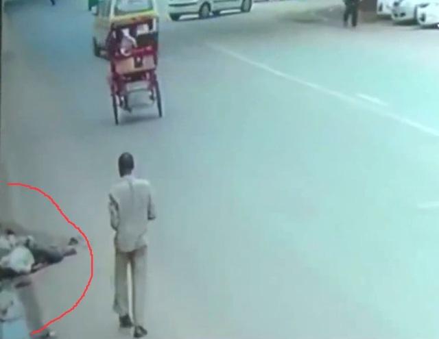 Nạn nhân (khoanh đỏ) bị bỏ mặc bên lề đường sau TNGT tại New Delhi, Ấn Độ.