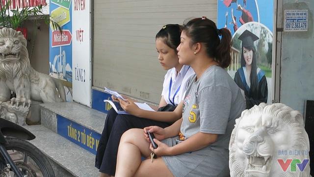 Tại điểm thi trường THPT Quang Trung - Đống Đa, nhiều học sinh tranh thủ giở sách ôn bài trong thời gian chờ thi.