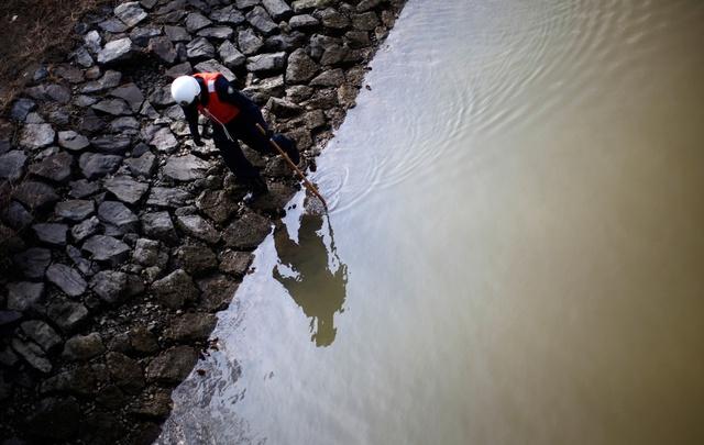 Cảnh sát Nhật Bản tìm kiếm thi thể nạn nhân trong một khu vực bị tàn phá bởi trận động đất - sóng thần ngày 11/3/2011 ở Rikuzentakata. (Ảnh: Reuters)