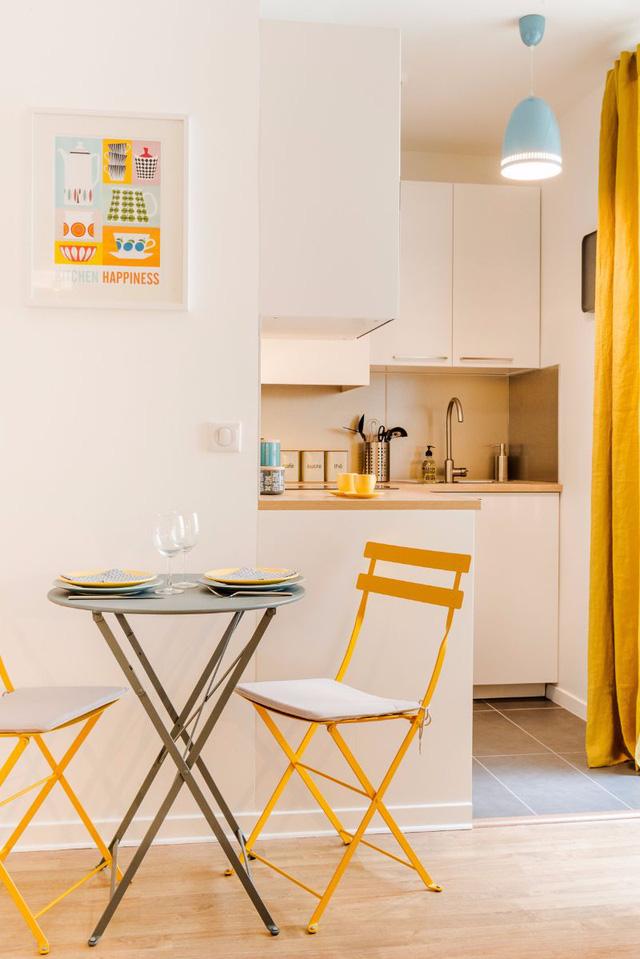 Tranh treo tường, ghế ngồi và rèm cửa đều mang màu vàng nổi bật, vô cùng hút mắt.
