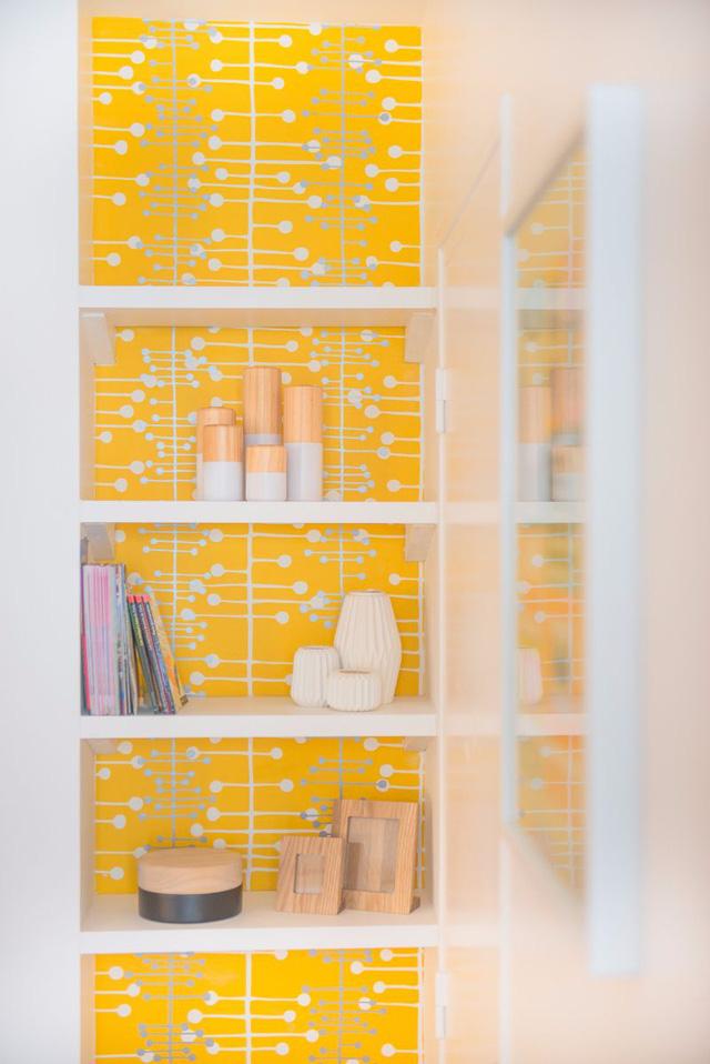 Để tiết kiệm diện tích, tủ tường âm màu vàng được sử dụng bày sách và đồ trang trí.