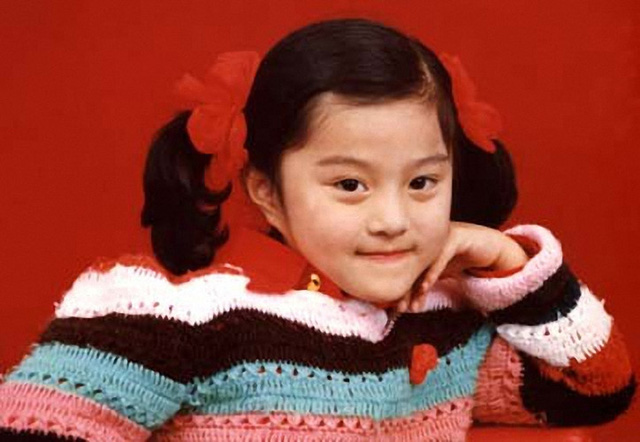 Lớn hơn một chút, Phạm Băng Băng đã biết làm điệu với tóc bím 2 bên buộc nơ đỏ xinh xắn.