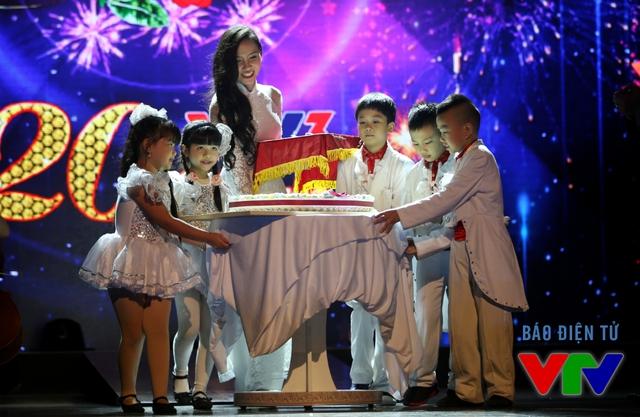 MC Minh Hà xuất hiện duyên dáng trong tà áo dài trắng. Cô cùng các em nhỏ đưa chiếc bánh sinh nhật mừng tuổi 20 của VTV3 lên sân khấu.