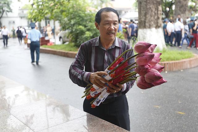 Bên ngoài nhà tang lễ, một người dân chuẩn bị 9 bông hoa sen để tới viếng 9 thành viên trên chiếc máy bay CASA 212 hi sinh khi làm nhiệm vụ. Ông cho biết không có quan hệ thân thích gì với 9 liệt sỹ.