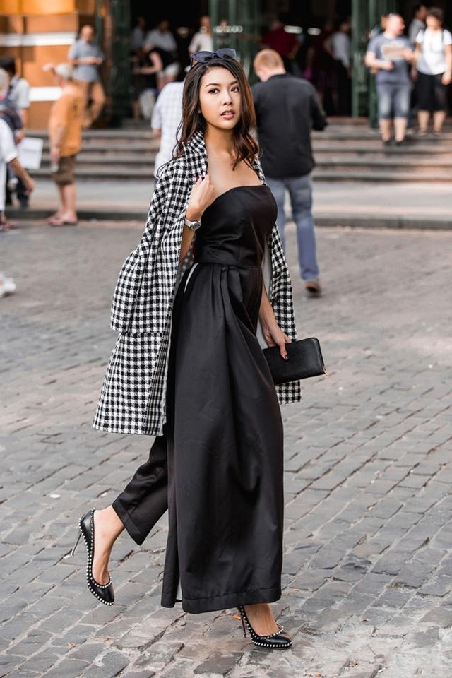 Thúy Vân khoe dáng với jumpsuits phối sáng tạo giữa áo cúp ngực và quần oversize. Áo khoác hờ họa tiết ca-rô đen trắng làm điểm nhấn.