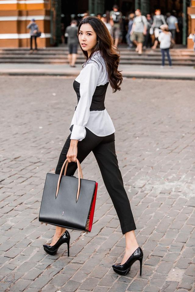 Giày cao gót mũi nhọn ăn nhập cùng bộ cánh tối màu. Túi xách cùng màu tạo tổng thể lịch thiệp.