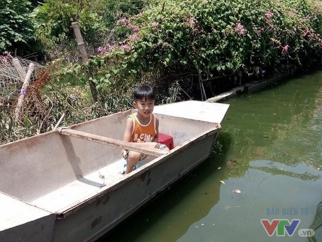 Nhiều gia đình phải dùng thuyền để chở trẻ em qua chỗ ngập sâu