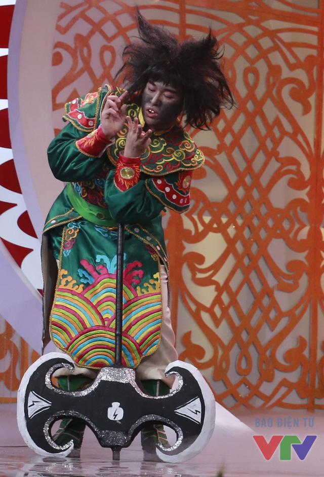 """Trong Táo quân 2016, Minh Quân tiếp tục có tạo hình răng hô, mặt đen và tóc xù. Ngoài ra, diễn xuất của anh cũng gây cười vì dáng đi ngúng nguẩy hay cách nói luyến """"vâng""""."""