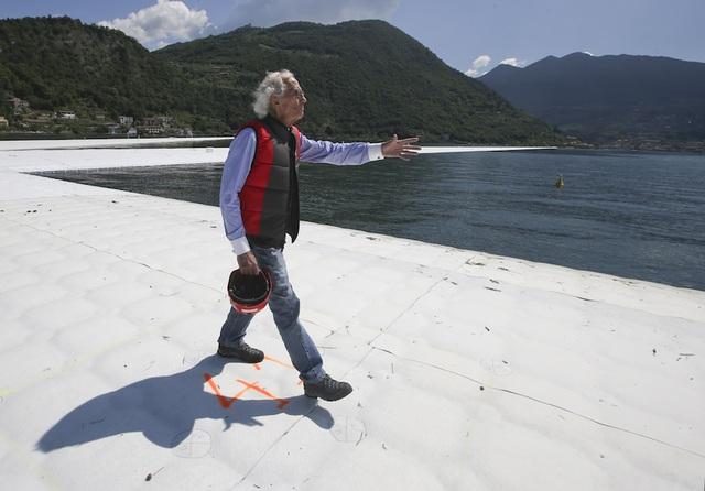 Christo bước trên The Floating Piers khi chiếc cầu phao còn chưa được phủ lớp vải màu cam (Ảnh: AP)