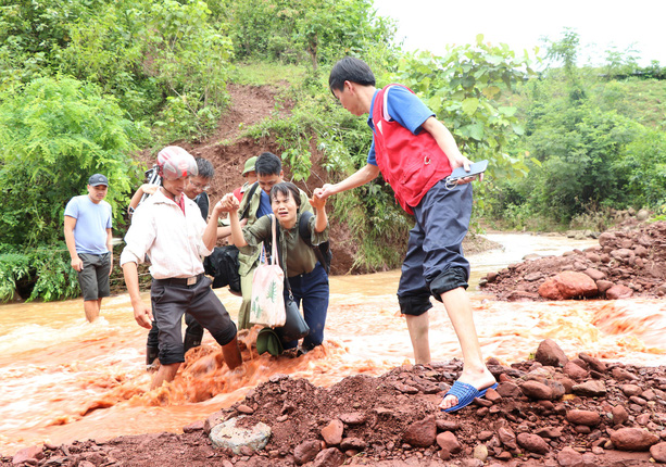 PV Nguyễn Ngân VTV cùng các đồng nghiệp băng qua dòng suối dữ để đưa tin về công tác tìm kiếm người mất tích
