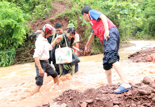 PV Nguyễn Ngân VTV cùng các đồng nghiệp băng qua dòng suối giữ để đưa tin về công tác tìm kiếm người mất tích