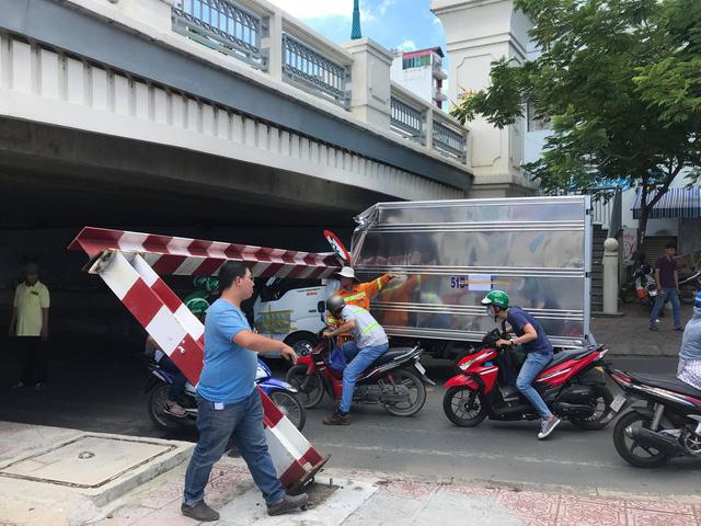 TP.HCM: Xe tải kéo ngã thanh giới hạn chiều cao dưới gầm cầu Bông - Ảnh 1.