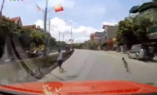 Theo chân người lớn băng qua đường, em nhỏ suýt gặp tai nạn - Ảnh 1.