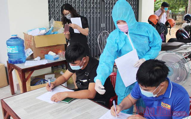 A health worker guides travellers on completing mandatory health declarations when traveling through Quang Tri. (Photo: NDO/Lam Quang Huy)