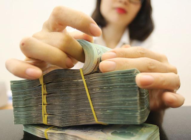 Tiền gửi chảy mạnh vào ngân hàng, lãi suất tiết kiệm giảm liên tiếp - Ảnh 1.