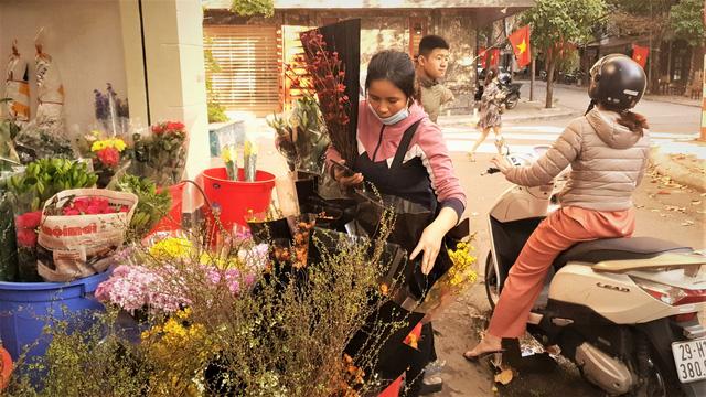 Người dân Hà Nội hối hả mang hoa về nhà trong ngày cuối của năm Âm lịch - Ảnh 2.