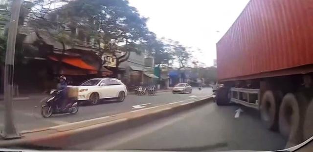 Cố lách vượt xe container, tài xế xe máy bị ngã gãy chân - Ảnh 1.