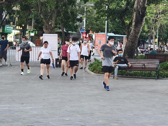 Hà Nội: Trên hồ Hoàn Kiếm nhiều người vẫn vô tư tập thể dục, hồ Tây đã giảm bớt - Ảnh 1.