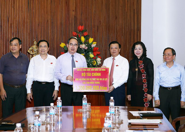 President of the Vietnam Fatherland Front Central Committee Nguyen Thien Nhan (third, left) and representatives from the Finance Ministry on October 21 (Photo: VNA)