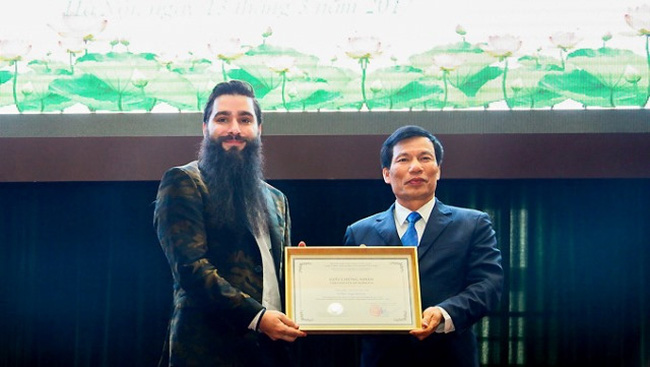 Minister of Culture, Sports and Tourism Nguyen Ngoc Thien hands over the decision of appointing Hollywood film director Jordan Vogt-Roberts as the tourism ambassador of Vietnam for the 2017-2020. (Credit: dulichvn.org.vn)
