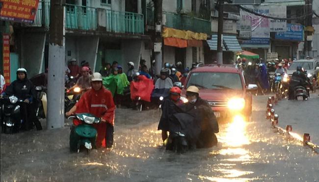 """Mưa """"siêu"""" lớn ở TP.HCM, người dân lội nước trên đường phố ngập nặng - ảnh 1"""