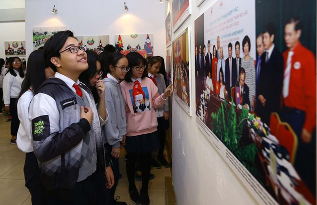 Students in Hanoi look at the photos of the exhibition (Photo: VNA)