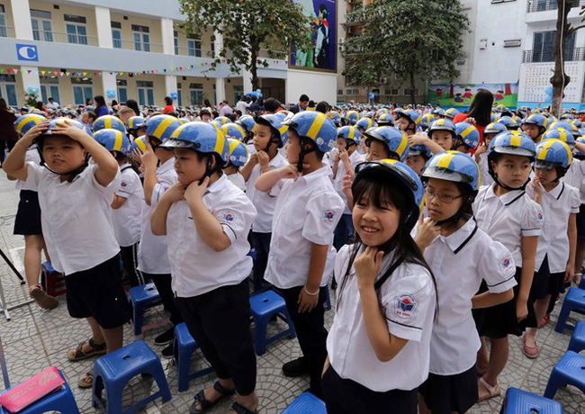 Students of the Ba Dinh Primary School in Hanoi are presented with helmets on November 8 (Photo: VNA)